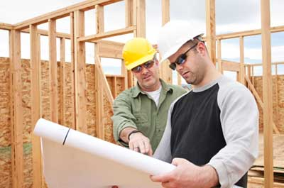Builder reviewing construction plans for cellulose insulation installation