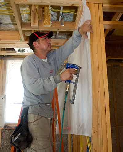 Insulation contractor preparing home for cellulose insulation installation